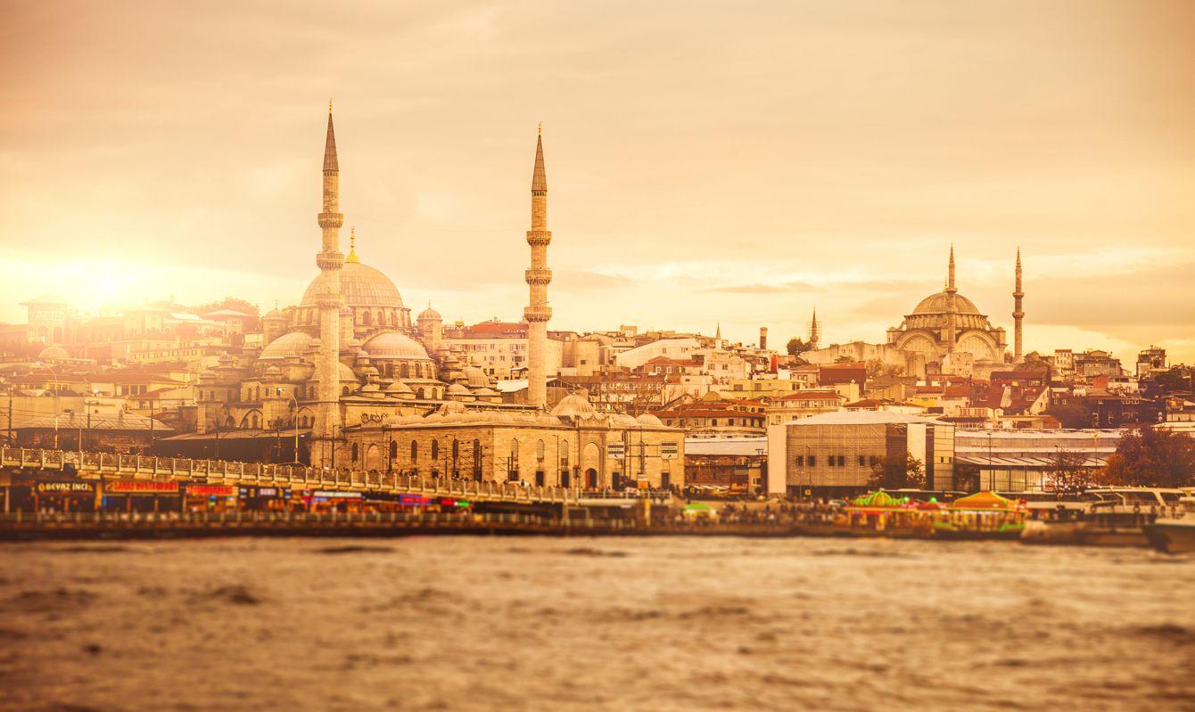 Istanbul cityscape at dusk exterior view of Yeni Camii and Galata Bridge.