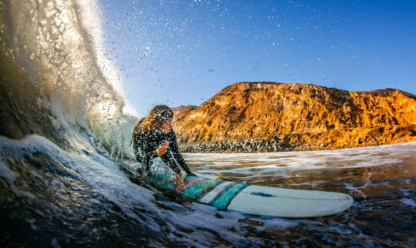 Teenage girl (16-17) riding longboard through water tube on Maibu coast, California, USA