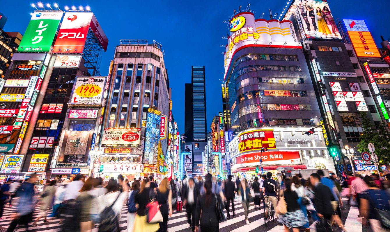 Crowded streets of Shinjuku shopping district with blurred commuters at dusk